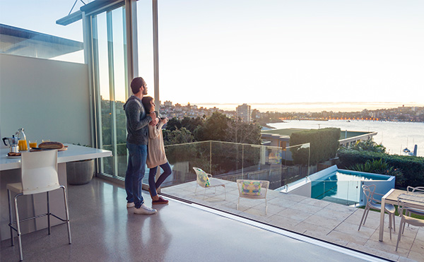A couple together in a luxury home looking out over Sydney Harbour